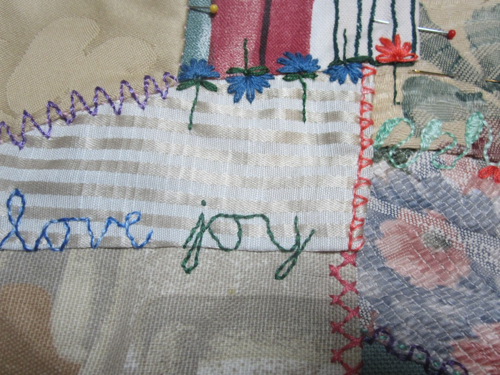 A small section from one of my crazy quilts showing cursive handwriting as a type of stitch