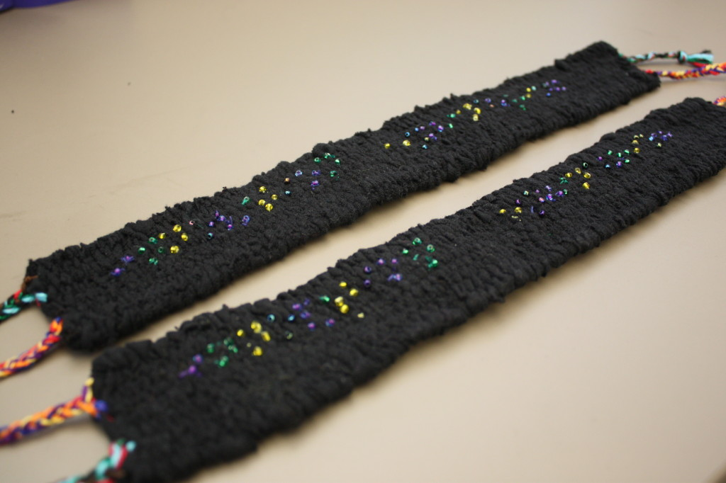 "Braille for ""Innovation Engineering"" made with seed beads on black belts"