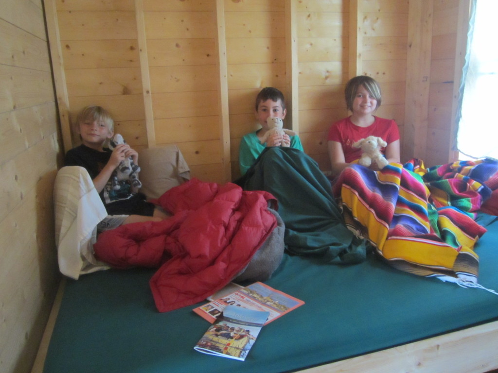 Kids playing on double bed area of treehouse