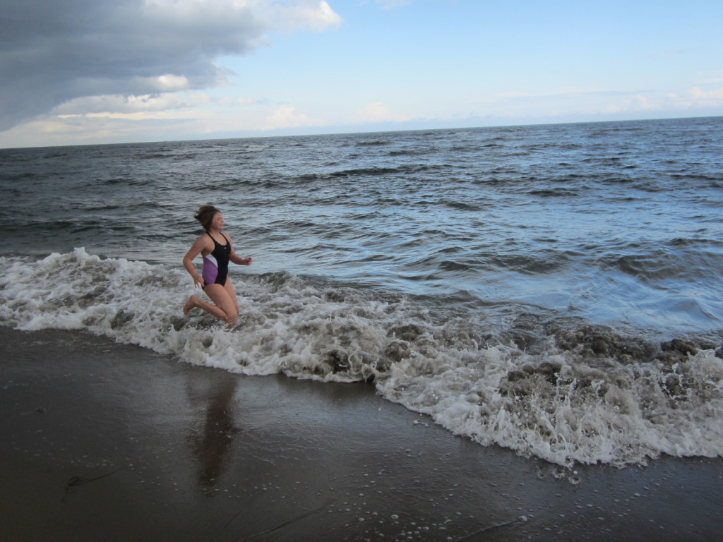 Nora runs in the waves at Kouchibouguac National Park