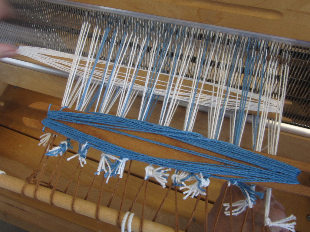 Stick shuttles going through my class mate's weaving project