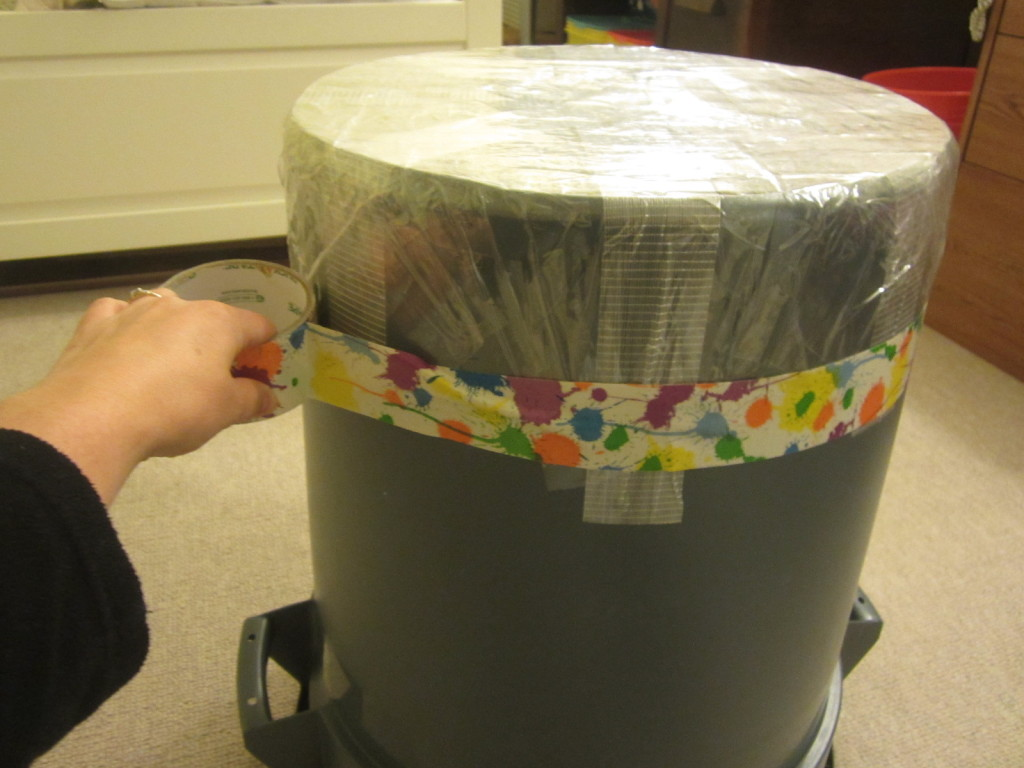 Adding the duct tape to the garbage can taiko drum