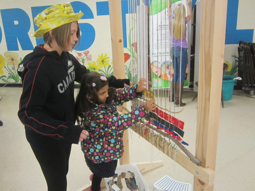 Nora teaches how to weave on the Story Loom