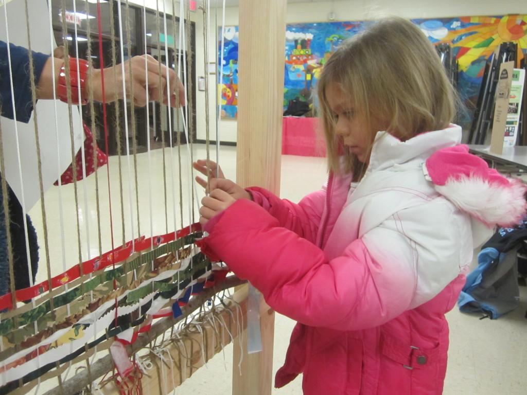 Little girl weaves on the Story Loom