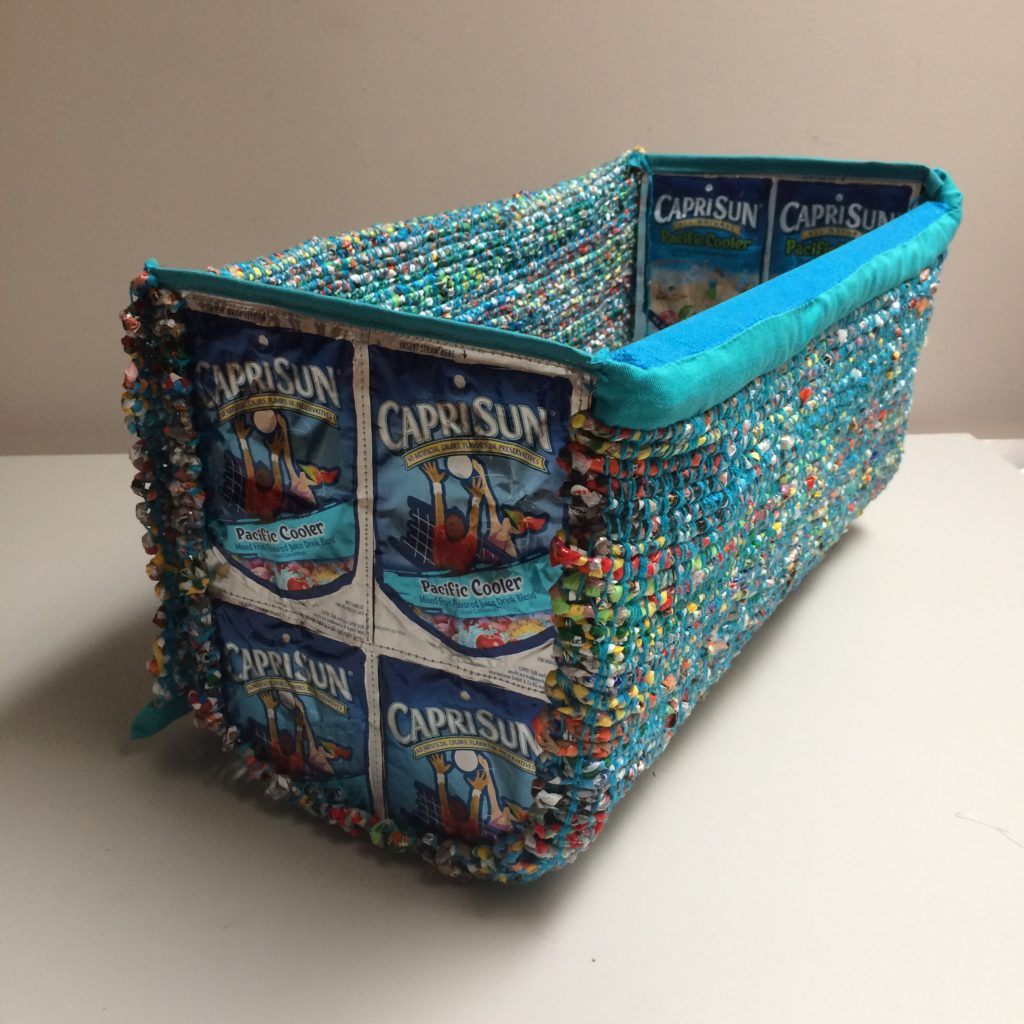Storage basket made from woven plastic bags, clementine wooden box and juice pouches by Trashmagination