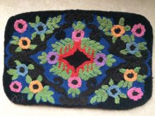 Rectangular hooked rug with pink, purple, blue and orange flowers in a traditional design