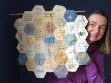 Quilter holds up small quilt made from hexagon-shaped blocks with messages of encouragement sewn on each block