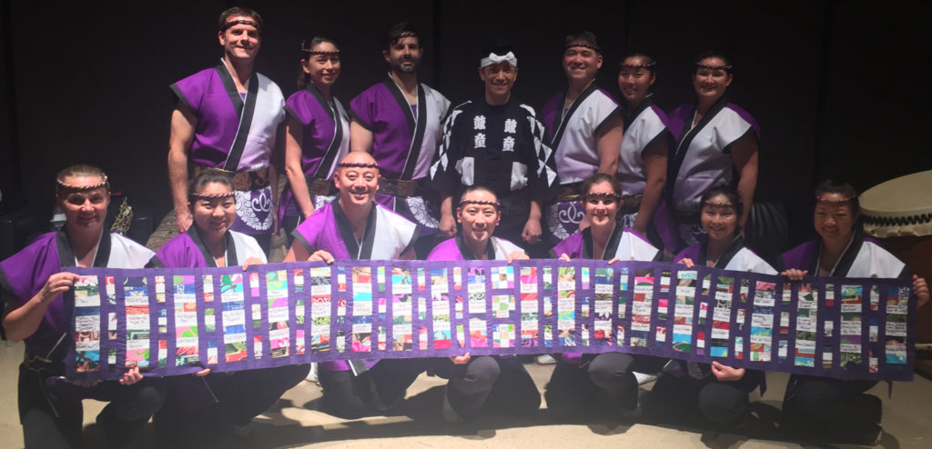 Members of Nen Daiko hold up a quilt showing the names of our supporters