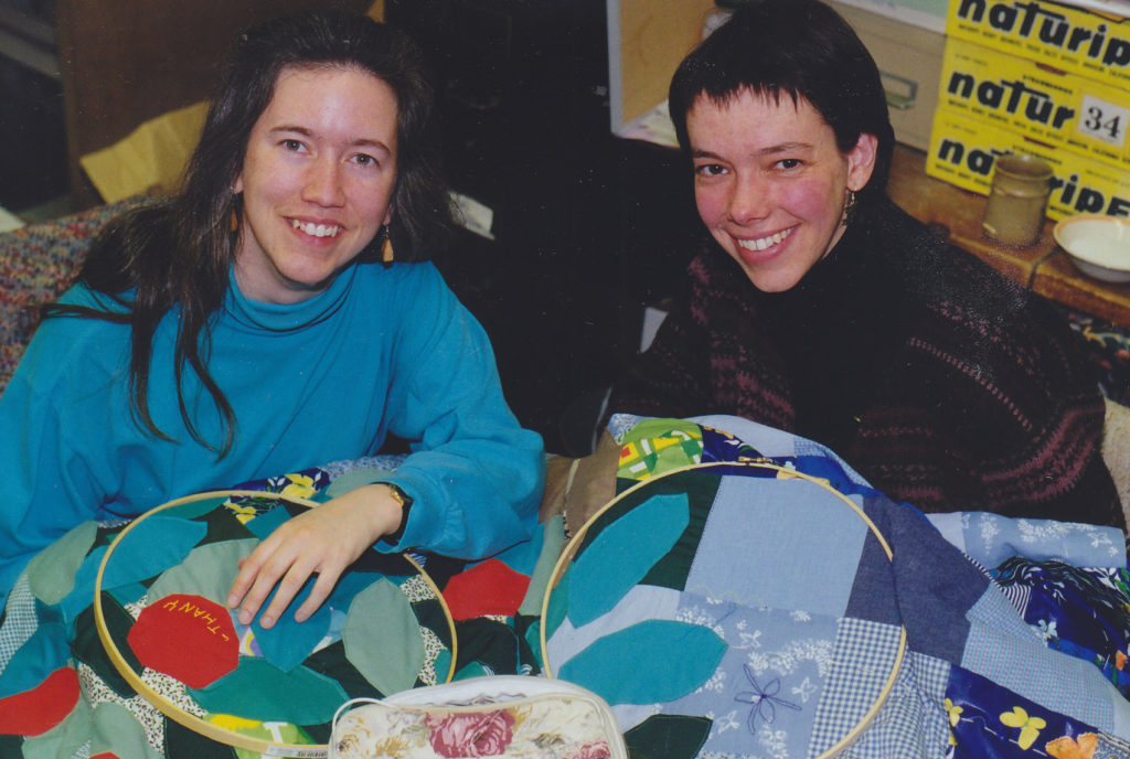 Two women help quilt a quilt for the Peace and Environment Resource Center