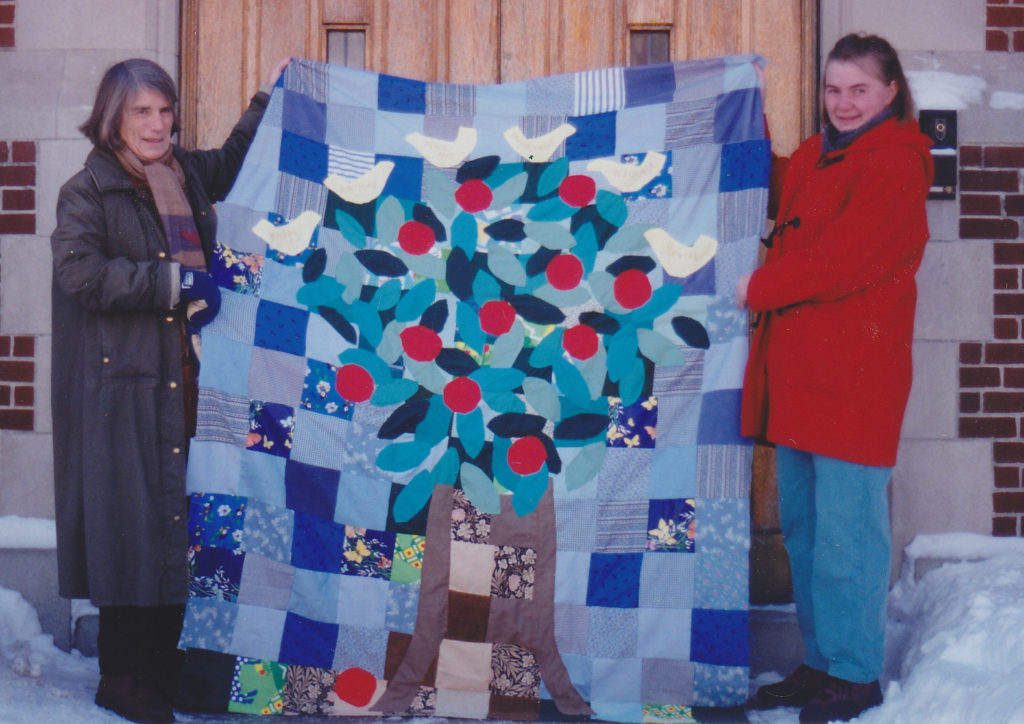 Two women hold up a quilt showing a tree with leaves, apples and birds on it made from scrap fabrics