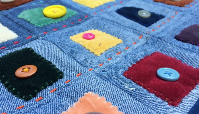 Denim quilt sewn with patches of velvet and decorative buttons