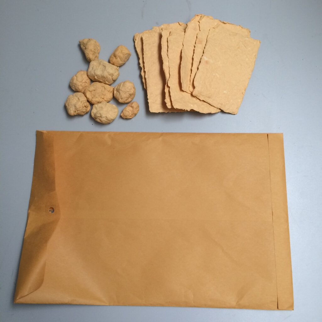 Yellow paper and pulp balls with a manila envelope which was the source of the pulp