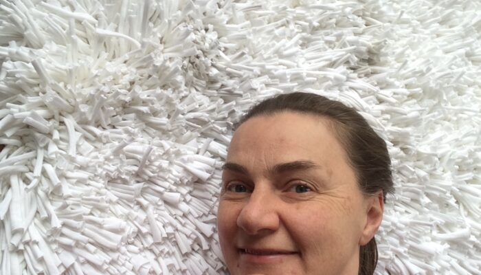 Happy Carla Brown from Trashmagination with her white rug woven from recycled t-shirts