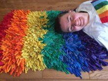 Woman laying on a very fluffy rug made from recycled tshirts in rainbow colors