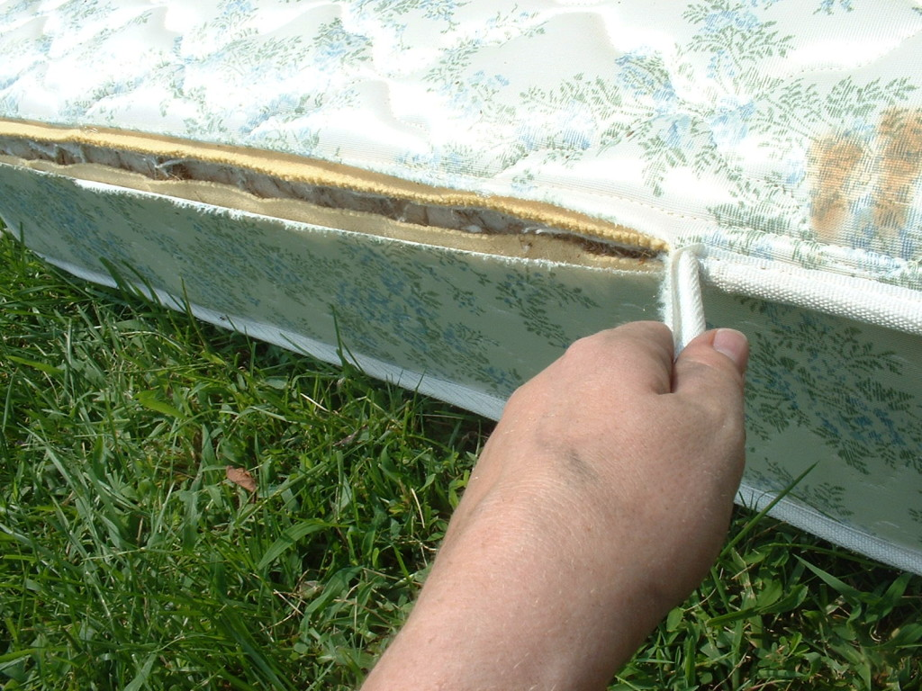 Removing the cord from the edge of the mattress