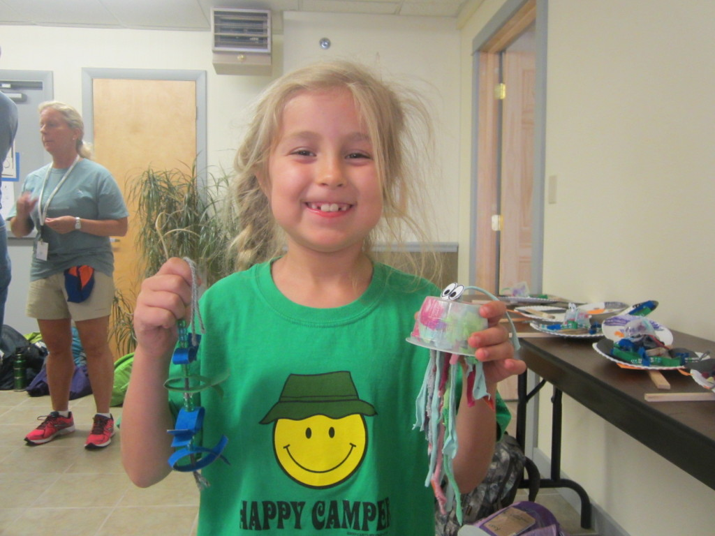 Camper showing her recycled crafts - toilet paper roll fish and applesauce container jellyfish
