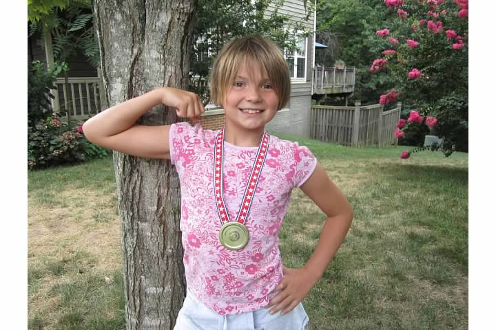 Nora models her Olympic medal made from a metal lid, July 2012