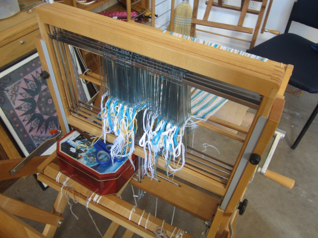 Warp fully threaded through the heddles