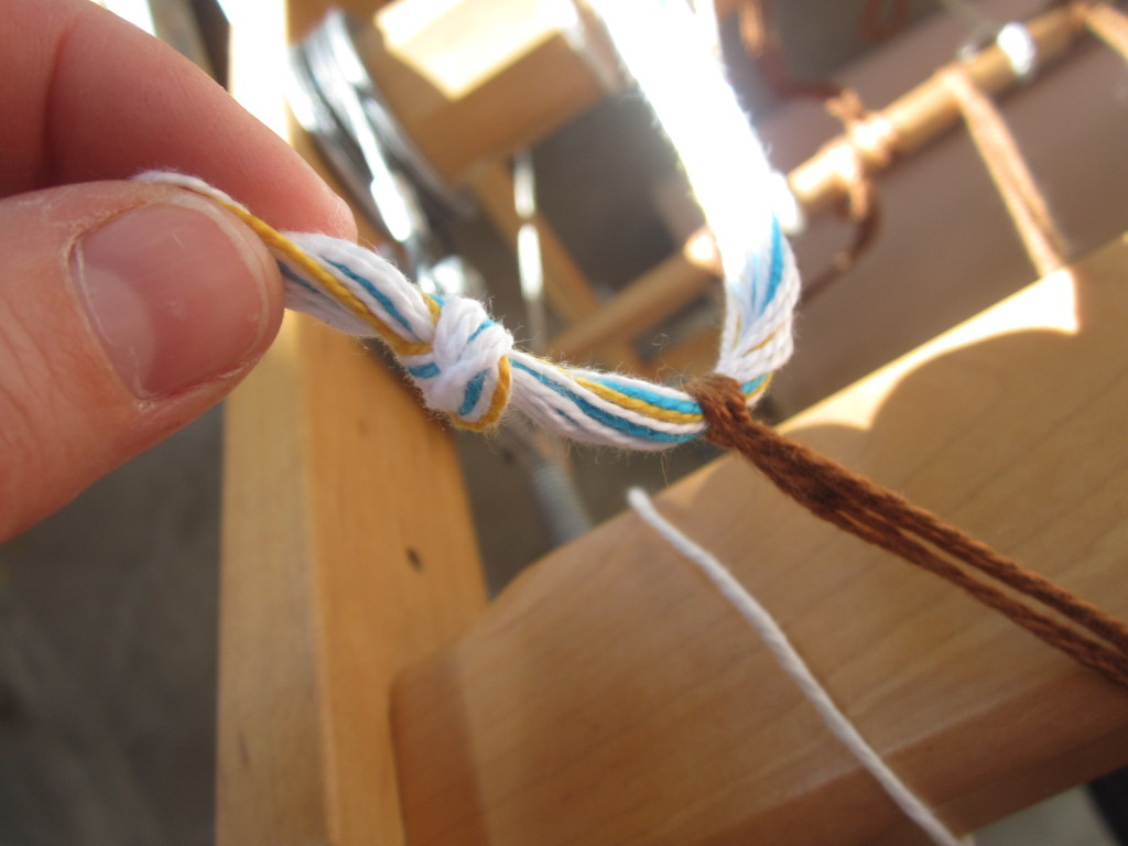 Cutting off the knots at the end of the warp