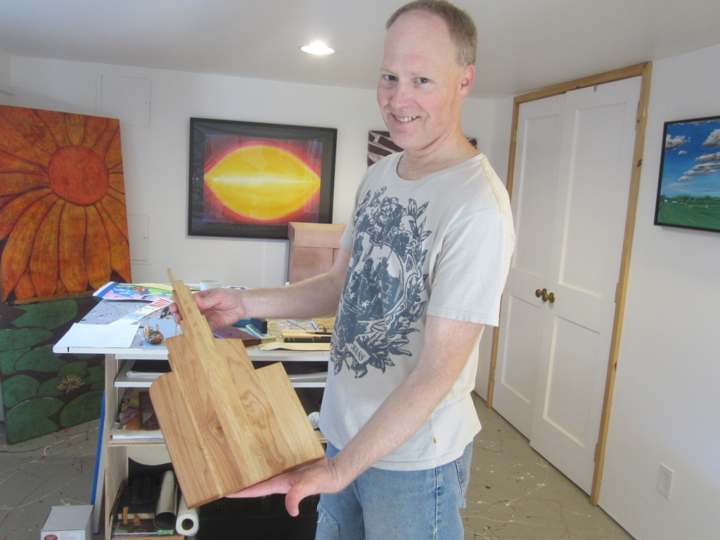 Dale Hoffmeyer in his home studio, holding one of his cutting boards made from recycled wood pieces