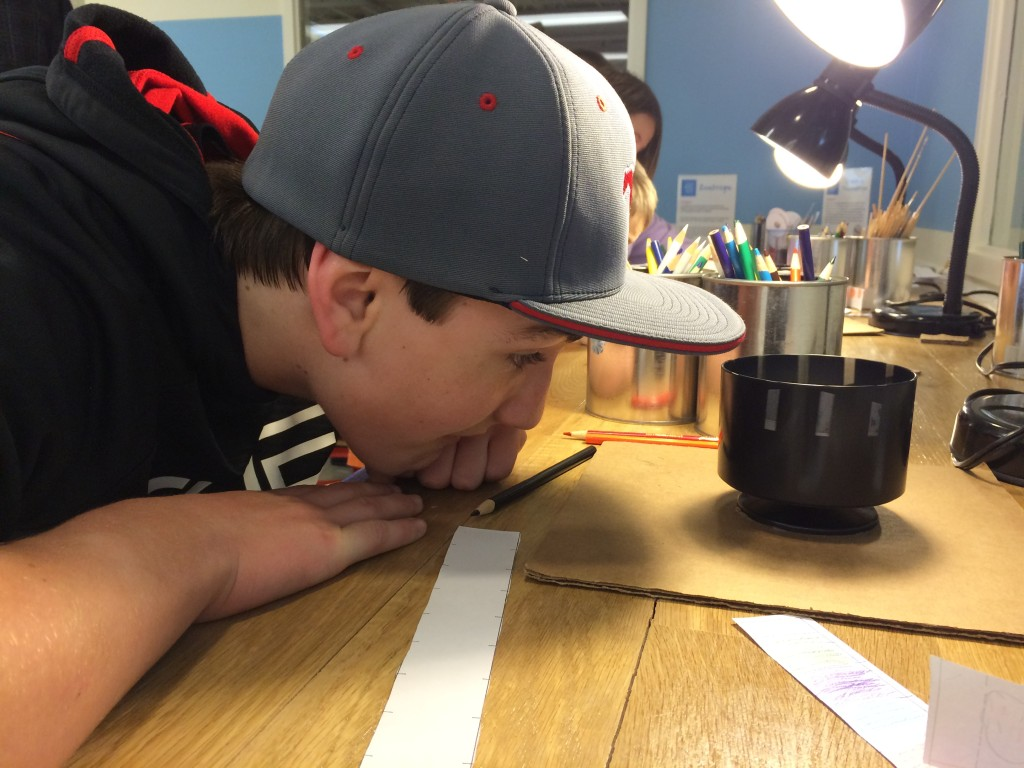 Noah checks out a zoetrope or device for making simple animation