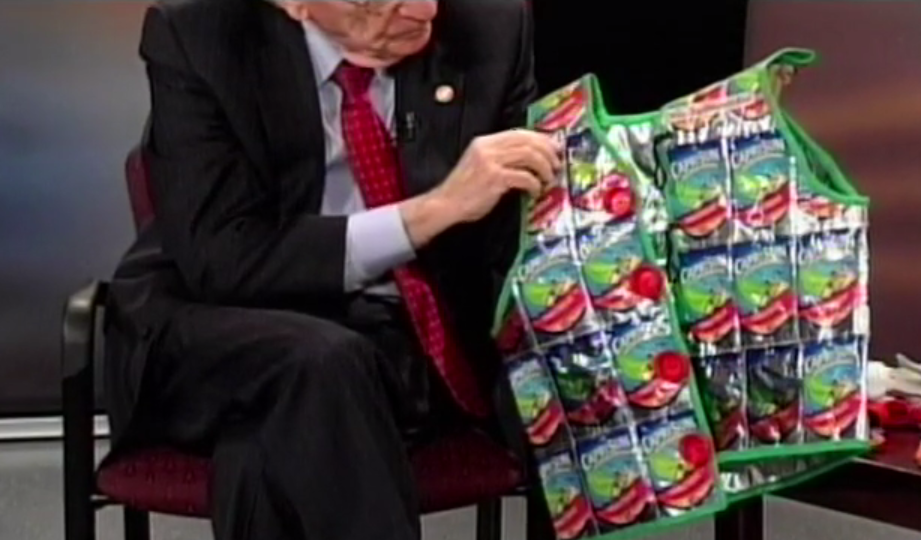 Delegate Ken Plum examines a vest made from juice pouches and plastic caps