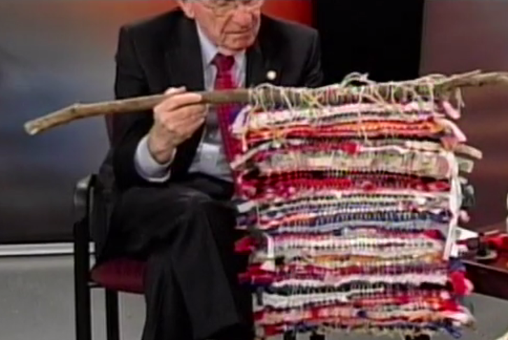 Delegate Ken Plum shows a weaving made at the Maker Faire from recycled materials
