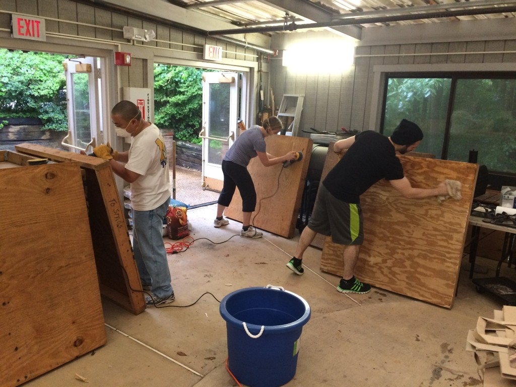 Three apprentices sanding components of our stage, preparing for the Obon Festival