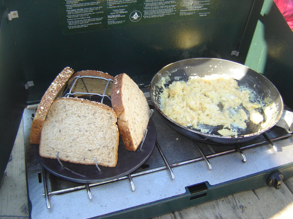 Cooking breakfast on a Coleman two-burner stove