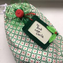 Environmentally-friendly gift wrapping - fabric bag, reusable gift tag, bow from recycled 2L bottle and cap - designed by Trashmagination