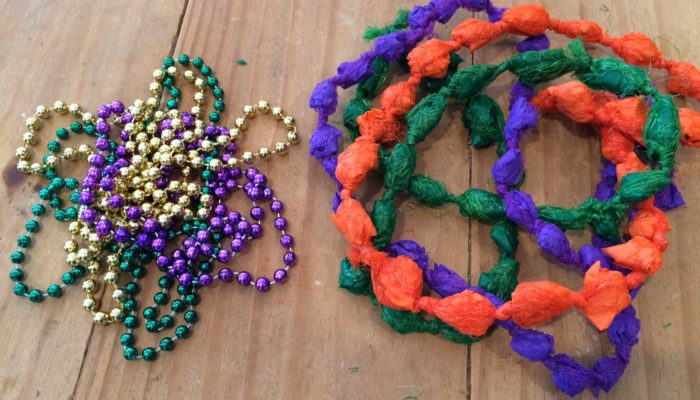 Typical Mardi Gras beads beside DIY Mardi Gras beads from plastic produce bags and table cloths - designed by Trashmagination