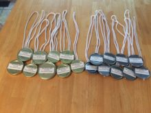 Gold and silver medals made from recycled lids and rope shopping bag handles