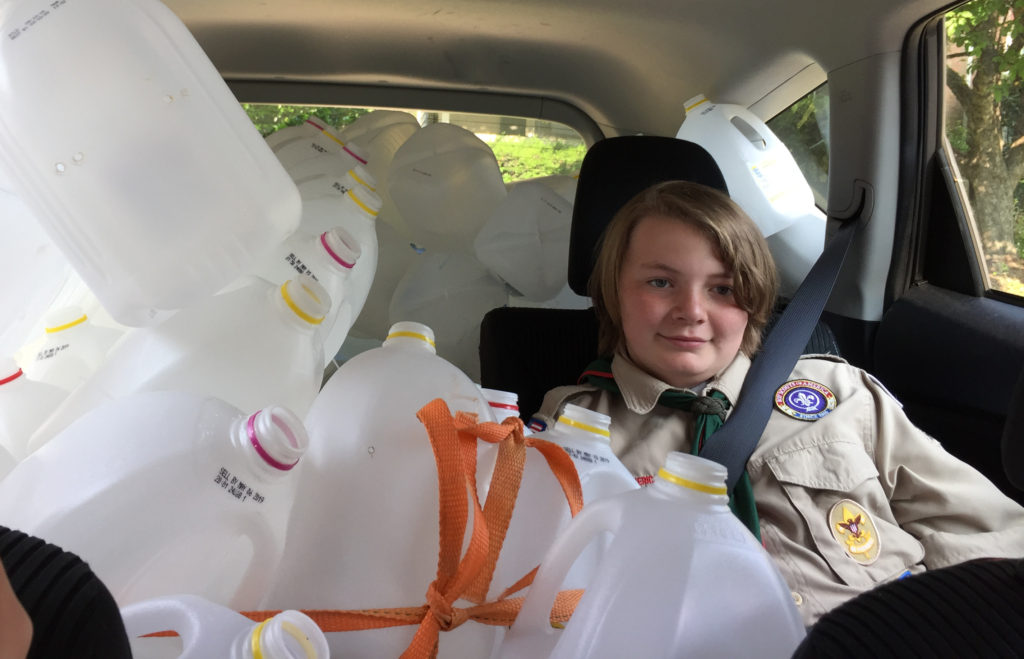 My son in the car surrounded by milk jugs on the way to the Maker Faire