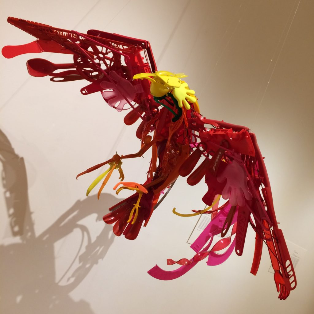 A red bird of paradise with a yellow head sculpture made from recycled plastic