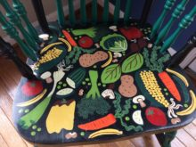 Seat of a rocking chair colorfully painted by Trashmagination - decorated with vegetables - called the Vege-chair