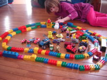 Girl playing with large plastic blocks and toy cars