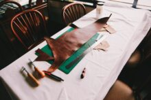 Table with large scrap of leather on top of a cutting board with many tools