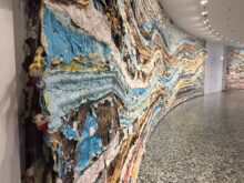 View of Mark Bradford's work Pickett's Charge at the Hirshhorn Sculpture Museum - photo shows many layers of papers and ropes along a curved wall to make a colorful mural