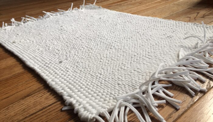 White rug woven from recycled t-shirts by Trashmagination