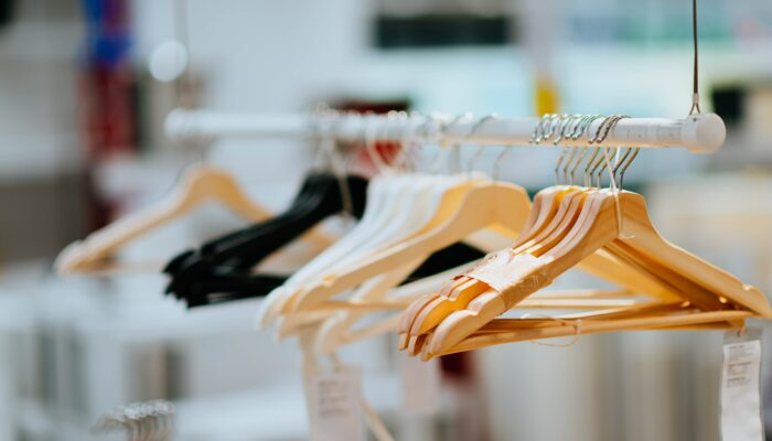 Wooden and plastic hangers on a clothing rack